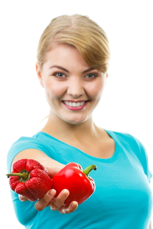 food on white: Happy woman holding in hand fresh and old wrinkled peppers, healthy and unhealthy food, white background