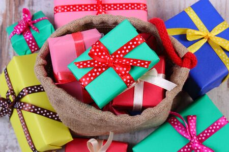 holiday tradition: Heap of wrapped colorful gifts for Christmas, birthday or other celebration in jute bag lying on old wooden white plank