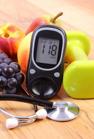 diabetes: Medidor de glucosa con el estetoscopio médicos, frutas y pesas para usar en la aptitud, el concepto de la diabetes, estilos de vida saludables y la nutrición Foto de archivo
