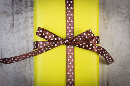 yellow paper: Wrapped in yellow paper gift for Christmas, birthday or other celebration on old wooden white plank