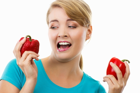 disgusted: Unhappy and disgusted woman with fresh peppers in hand looking at old wrinkled peppers, healthy and unhealthy food, white background
