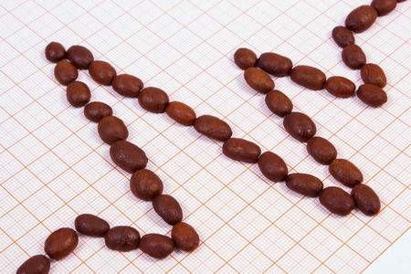 ecg heart: Electrocardiogram line of brown roasted coffee grains on graph paper, ecg heart rhythm, medicine and healthcare concept