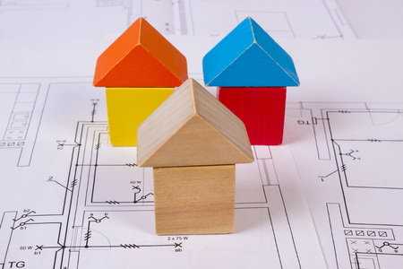project property: Houses shape made of wooden blocks lying on electrical construction drawings of house, concept of building house, drawing for projects