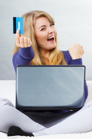 over paying: Happy woman holding credit card using laptop sitting on sofa, paying over internet for online shopping, typing on computer keyboard, surfing internet Stock Photo