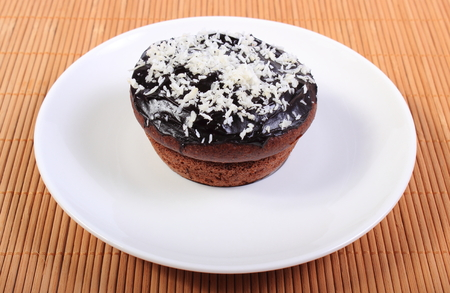 desiccated: Homemade delicious fresh baked chocolate muffins with desiccated coconut lying on white plate