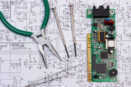 microelectronics: Printed circuit board with electrical components and precision tools lying on construction drawing of electronics, drawings and precision tools for engineer jobs, technology Stock Photo