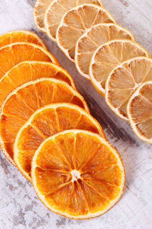lemon slices: Slices of fresh dried lemon and orange lying on old rustic wooden background Stock Photo