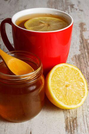 inmunidad: Lim�n fresco, miel en frasco de vidrio y una taza de t� caliente en la vieja mesa de madera blanca, alimentos saludables, fortalecer la inmunidad y la terapia alternativa Foto de archivo