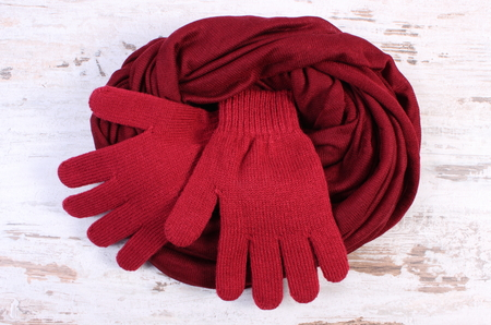 Pair of woolen gloves and shawl for woman on old rustic wooden background, womanly accessories, warm clothing for autumn or winter, burgundy color