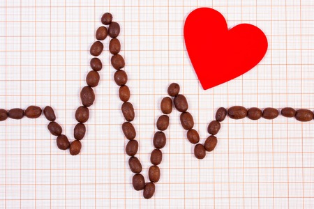 ecg heart: Electrocardiogram line of brown roasted coffee grains and red heart on graph paper, ecg heart rhythm, medicine and healthcare concept Stock Photo