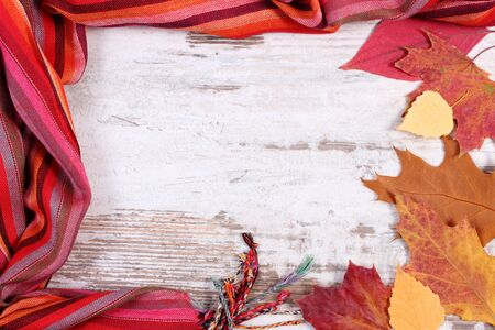 Frame of womanly woolen shawl and autumnal leaves, copy space for text, warm clothing for autumn or winter, old rustic wooden background
