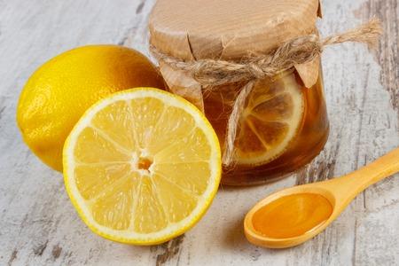 inmunidad: Frasco de vidrio con lim�n y miel, lim�n y miel en la cuchara de madera situada en la vieja mesa de madera blanca, la comida sana y el fortalecimiento de la inmunidad