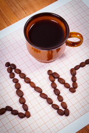 ecg heart: Electrocardiogram line of roasted coffee grains and cup of hot coffee on graph paper, ecg heart rhythm, medicine and healthcare concept