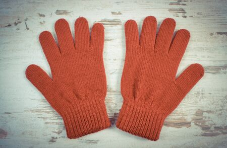 womanly: Vintage photo, Pair of woolen gloves for woman on old rustic wooden background, womanly accessories, warm clothing for autumn or winter, burgundy color