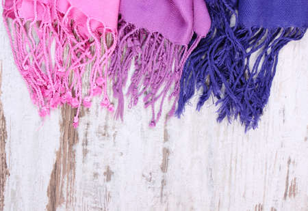 womanly: Colorful scarves with copy space for text, womanly accessories, warm clothing for autumn or winter, old rustic wooden background