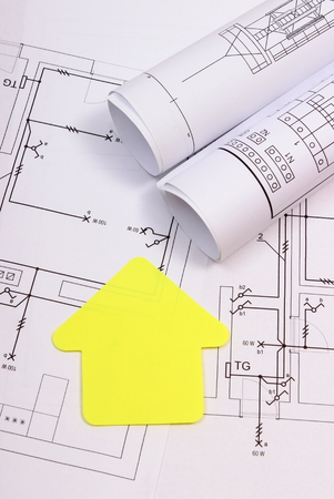 numbers: House of yellow paper and rolls of diagrams lying on electrical construction drawing of house, technology and concept of building home