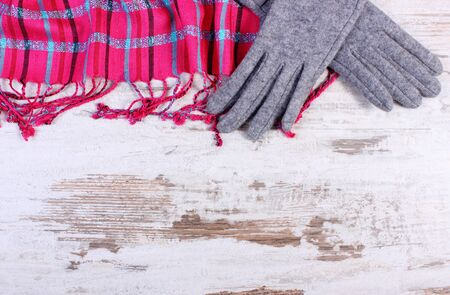 womanly: Frame of woolen gloves and colorful shawl with copy space for text, womanly accessories, warm clothing for autumn or winter, old rustic wooden background