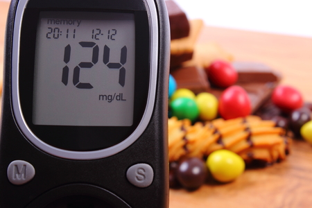 too many: Glucose meter with heap of candies and cookies on wooden table, too many sweets, concept of diabetes and reduction of eating sweets