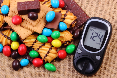 Glucose meter with heap of candies and cookies on jute burlap, too many sweets, concept of diabetes and reduction of eating sweets