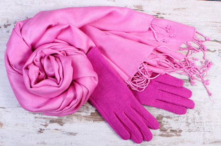 womanly: Woolen gloves and shawl for woman on old rustic wooden background, womanly accessories, warm clothing for autumn or winter Stock Photo