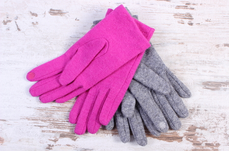 womanly: Pair of woolen gloves for woman on old rustic wooden background, womanly accessories, warm clothing for autumn or winter