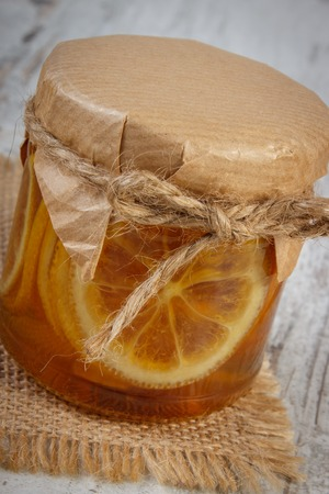 inmunidad: Lemon with honey in glass jar lying on old wooden white table, concept of healthy food, nutrition and strengthening immunity
