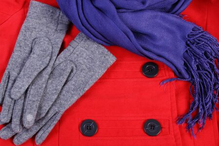 womanly: Woolen gloves and shawl for woman on red coat background, womanly accessories, warm clothing for autumn or winter