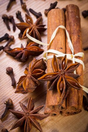 Star of anise, cinnamon sticks and cloves lying on wooden table, seasoning for cooking and baking