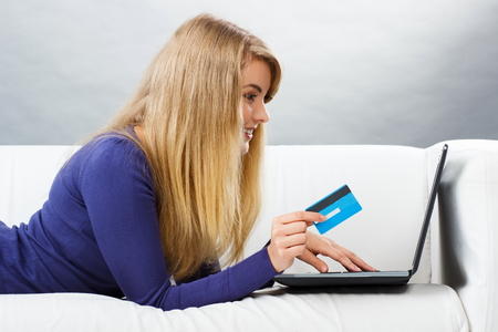 over paying: Happy woman holding credit card using laptop lying on sofa, paying over internet for online shopping, typing on computer keyboard, surfing internet