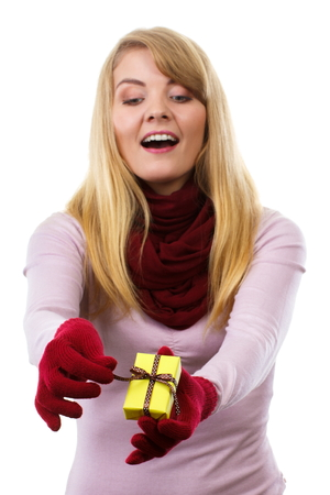 unwrapping: Happy woman in woolen shawl and gloves unwrapping gift for Christmas, valentine, birthday or other celebration, christmas time, white background