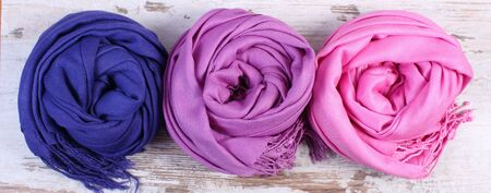 womanly: Colorful scarves on old rustic wooden background, womanly accessories, warm clothing for autumn or winter