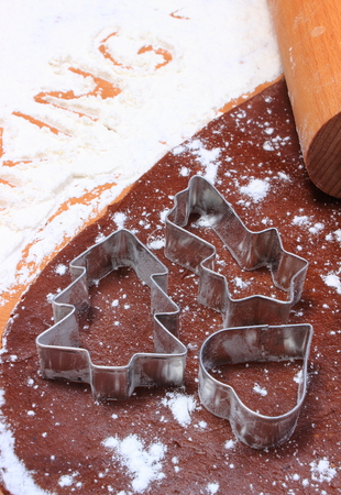 cookie cutters: Cookie cutters in shape of heart and christmas tree, rolling pin on dough for cookies and gingerbread, accessories for baking, christmas time