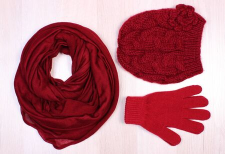 womanly: Womanly clothes on wooden surface plank, gloves, cap and shawl or scarf, warm clothing for autumn or winter