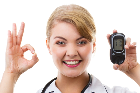 Happy woman holding glucose meter with positive result of measurement sugar level, concept of diabetes, checking sugar level, white background