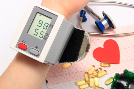 Measuring blood pressure, heart shape, stethoscope and tablets on electrocardiogram, medicine concept Stock Photo