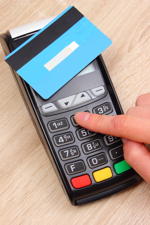 personal banking: Hand of woman using payment terminal with contactless credit card, enter personal identification number, credit card reader, finance and banking concept
