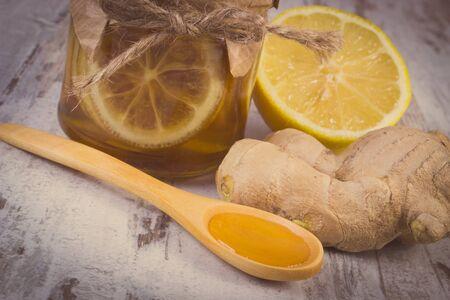 inmunidad: Foto de la vendimia, de lim�n con miel en frasco de vidrio, lim�n, la miel en la cuchara de madera y el jengibre en tabla de madera, el concepto de la comida sana, la nutrici�n y la inmunidad fortalecimiento