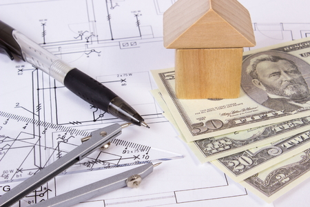 investment banking: House shape made of wooden blocks, accessories for drawing and currencies dollar on electrical construction drawings, concept of building house, drawing for projects