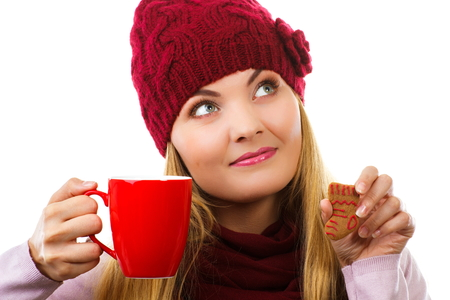 tea and biscuits: Dreaming woman in woolen cap and shawl with decorated gingerbread or christmas cookies and red cup of hot tea, christmas time, white background