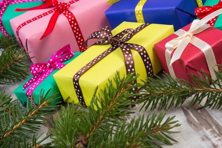 anniversaire: cadeaux color�s Emball� pour No�l, anniversaire ou toute autre c�l�bration et vert branches de sapin sur vieille planche en bois blanc
