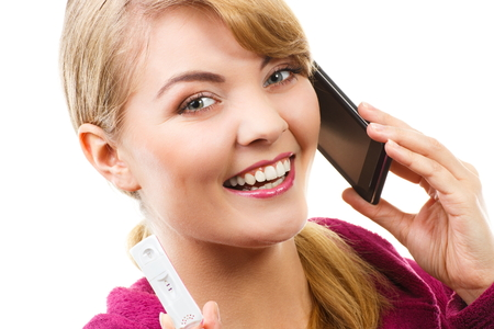 informing: Happy delighted woman showing pregnancy test and talking on mobile phone, informing someone about positive result test, expecting for baby