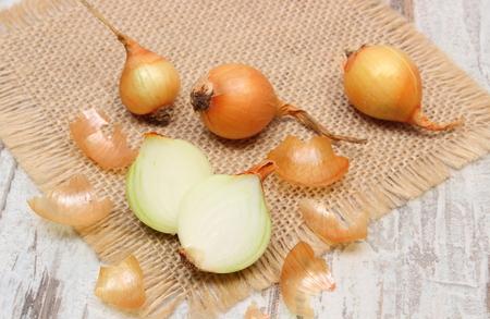 inmunidad: Cebollas org�nicas frescas sobre tela de yute sobre fondo de madera vieja, la alimentaci�n sana y el fortalecimiento de la inmunidad