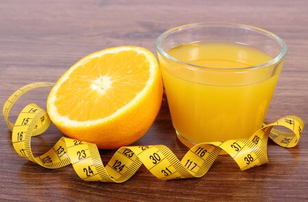 immunity: Fresh ripe orange, glass of juice and tape measure on wooden surface plank, healthy lifestyles nutrition and strengthening immunity