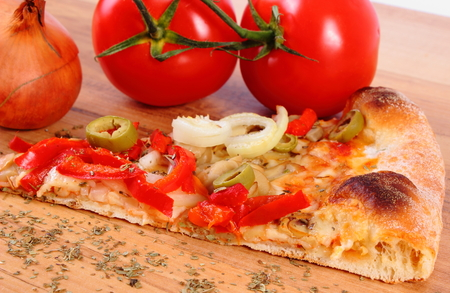 fast meal: Slice of fresh baked vegetarian pizza ready to eat, tomatoes onion and basil on wooden table, italian cuisine, concept of fast food Stock Photo