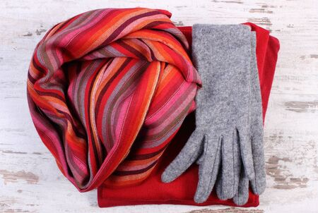 womanly: Womanly clothes, gloves shawl sweater, warm clothing for autumn or winter, old rustic wooden background Stock Photo