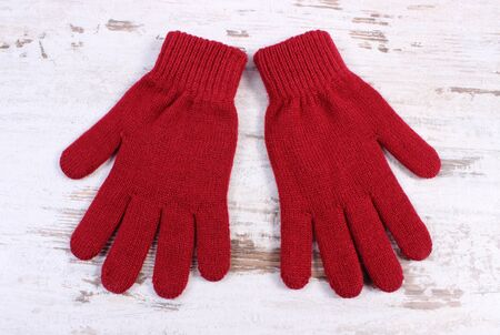 womanly: Pair of woolen gloves for woman on old rustic wooden background, womanly accessories, warm clothing for autumn or winter, burgundy color Stock Photo