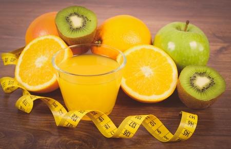 immunity: Vintage photo, Fresh ripe fruits, glass of juice and tape measure on wooden surface plank, grapefruit orange kiwi apple, healthy lifestyles nutrition and strengthening immunity