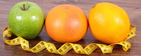 inmunidad: Frutas maduras y cinta m�trica en tabl�n de madera de superficie, naranja pomelo manzana, estilo de vida saludable y la nutrici�n fortalecimiento de la inmunidad