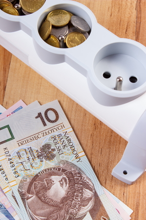 energy costs: Electrical power strip and polish currency on wooden floor, power board, concept of saving money on electricity, energy costs