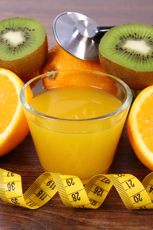inmunidad: Medical stethoscope and tape measure with fresh ripe fruits and glass of juice on wooden surface plank, grapefruit orange kiwi, healthy lifestyles nutrition and strengthening immunity